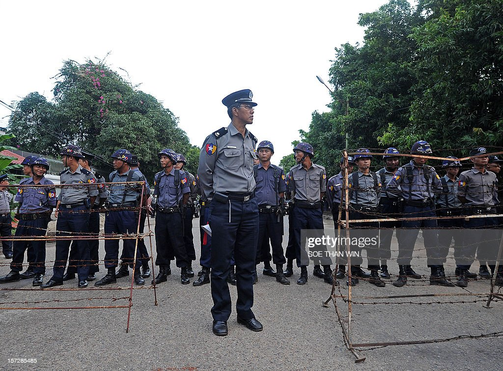 This picture taken on December 1, 2012 shows Myanmar police standing guard behind barbed wire in front of the Chinese embassy as protesters rally nearby in Yangon. Police apologised for injuring scores of monks in a crackdown on a protest against a Chinese-backed copper mine, but tensions over the pre-dawn raid remained high. AFP PHOTO / Soe Than WIN