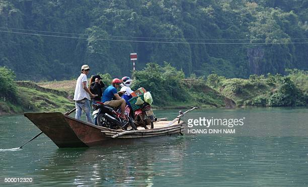 This picture taken on December 1 2015 shows local residents crossing a river on a boat at the national park Phong Nha Ke Bang in the central coastal...