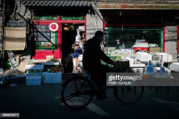 This picture taken on December 1 2016 shows a man riding his bicycle past a convenience store in a hutong in Beijing With space scarce in the city of...