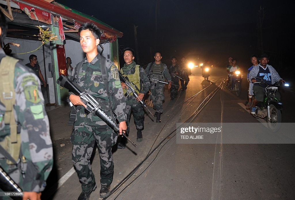 This picture taken on December 10, 2012 shows Philippine soldiers patrolling along the streets of the typhoon devastated town of Cateel, Davao Oriental. The United Nations launched a 65 million USD global appeal on December 10 to help desperate survivors of a typhoon that killed more than 600 people and affected millions in the southern Philippines. AFP PHOTO / TED ALJIBE