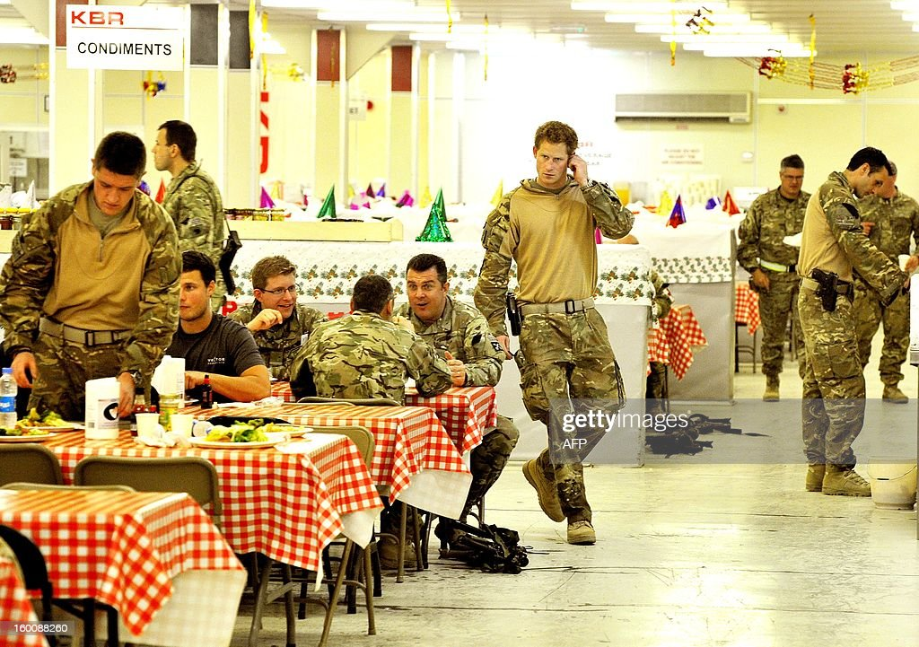 This picture taken on December 11, 2012 shows Britain's Prince Harry (R) walking past in the dining facility at Camp Bastion in Afghanistan's Helmand province. Prince Harry said he was 'thrilled to be back' in Britain as he returned home after serving a 20-week tour of duty in Afghanistan. The 28-year-old Apache attack helicopter co-pilot arrived back on home turf after spending two days' mandatory post-deployment 'decompression' time at a British base in Cyprus. AFP PHOTO/POOL/John STILLWELL - NOTE TO EDITORS THIS PICTURE IS HELD UNDER STRICT EMBARGO AND NOT TO BE RELEASED UNTIL AFTER 0001 GMT ON JANUARY 27, 2013