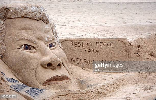 This picture taken on December 11 2013 shows a sand sculpture in tribute to late former South African President Nelson Mandela on Durban's beach...