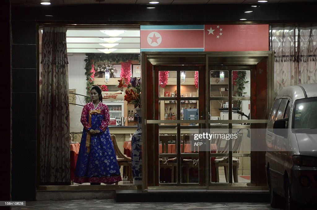 This picture taken on December 12, 2012 shows a North Korean hostess waiting for customers at the entrance to a restaurant in the Chinese border city of Dandong in China's northeastern Liaoning province. China is North Korea's biggest trading partner by far, and most of the business passes through Dandong in northeastern China, where lorries piled high with tyres and sacks are processed at the customs post.