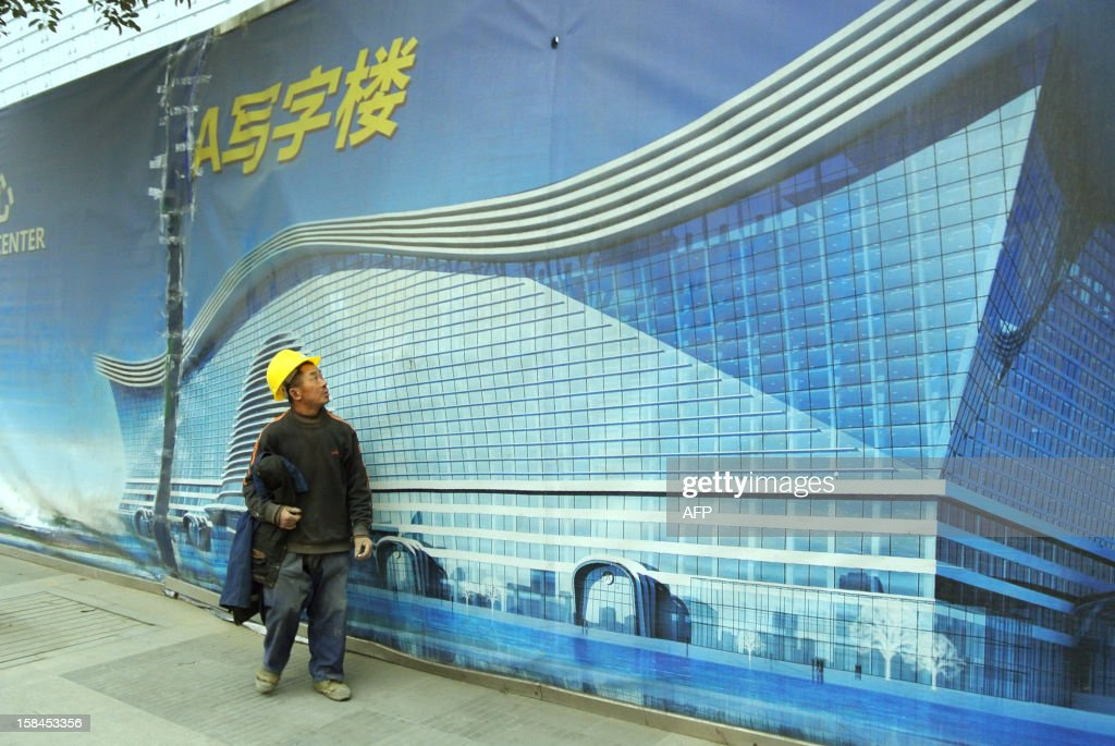 This picture taken on December 12, 2012 shows a worker walking past a billboard of the world's biggest standalone building which is now still under construction in Chengdu, southwest China's Sichuan province. The metropolis of Chengdu, the reference of the breathtaking economic growth in western China, embodies its ambition in the 'Global Center' building that is described as 'the largest single building in the world. '