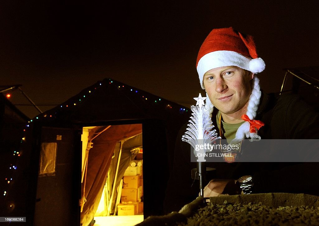 This picture taken on December 12, 2012 shows Britain's Prince Harry wearing a Christmas Hat as he stands outside the VHR (very high readiness) tent at Camp Bastion in Afghanistan's Helmand province. Prince Harry said he was 'thrilled to be back' in Britain as he returned home after serving a 20-week tour of duty in Afghanistan. The 28-year-old Apache attack helicopter co-pilot arrived back on home turf after spending two days' mandatory post-deployment 'decompression' time at a British base in Cyprus. AFP PHOTO/POOL/John STILLWELL - NOTE