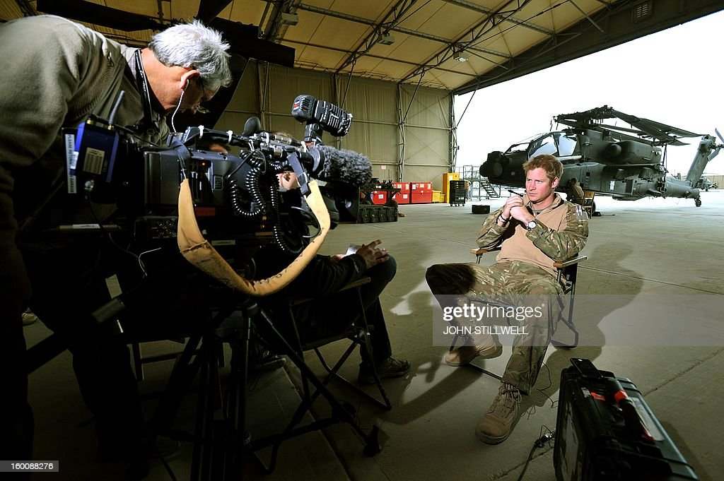 This picture taken on December 12, 2012 shows Britain's Prince Harry (R) giving an interview to a TV crew at Camp Bastion in Afghanistan's Helmand province. Prince Harry said he was 'thrilled to be back' in Britain as he returned home after serving a 20-week tour of duty in Afghanistan. The 28-year-old Apache attack helicopter co-pilot arrived back on home turf after spending two days' mandatory post-deployment 'decompression' time at a British base in Cyprus. AFP PHOTO/POOL/John STILLWELL - NOTE