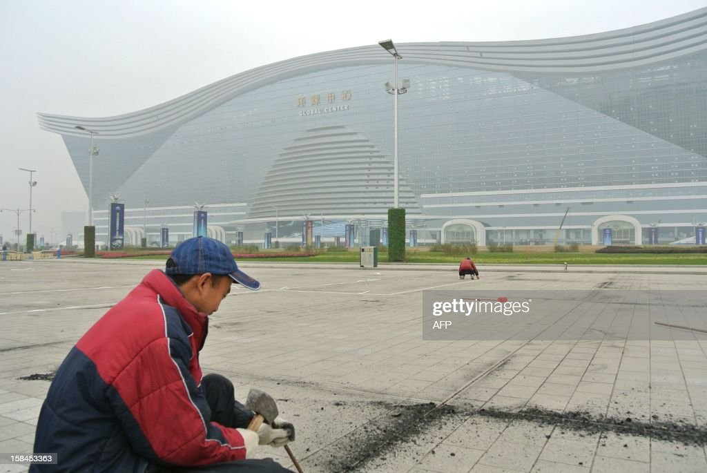 This picture taken on December 12, 2012 shows labourers working on a square outside the world's biggest standalone building which is now still under construction in Chengdu, southwest China's Sichuan province. The metropolis of Chengdu, the reference of the breathtaking economic growth in western China, embodies its ambition in the 'Global Center' building that is described as 'the largest single building in the world. '