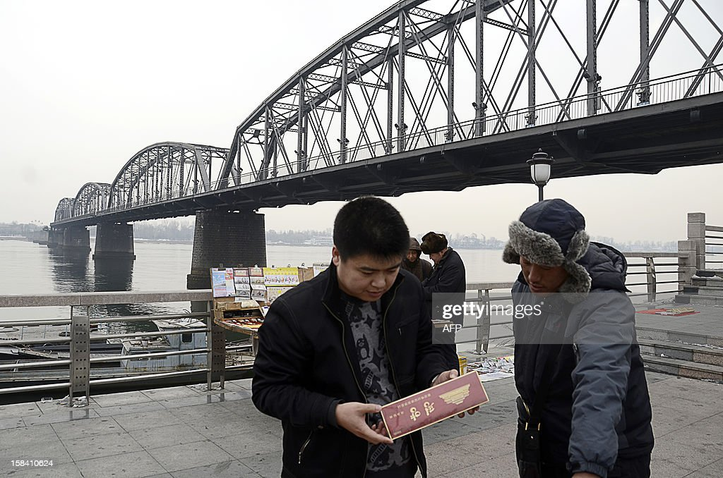 This picture taken on December 13, 2012 shows a Chinese man (L) looking at cigarettes for sale on the banks of the Yalu River in the northeastern Chinese border city of Dandong, in China's northeastern Liaoning province, across the river from North Korea (back L). China is North Korea's biggest trading partner by far, and most of the business passes through Dandong in northeastern China, where lorries piled high with tyres and sacks are processed at the customs post.