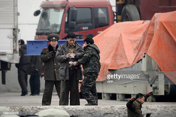 This picture taken on December 14 2012 from China's northeastern city of Dandong looking across the border shows North Korean soldiers at a river...