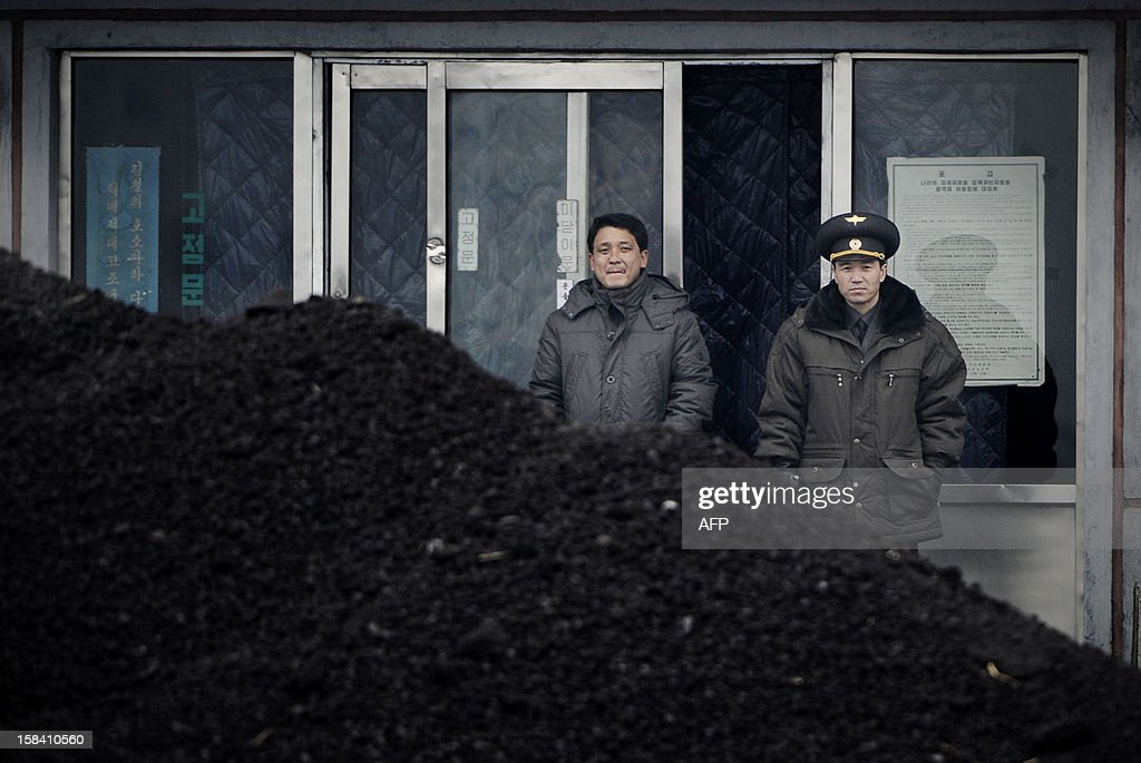 This picture taken on December 14, 2012 from China's northeastern city of Dandong, looking across the border, shows a North Korean military officer (R) and a North Korea man (L) standing behind a pile of coal along the banks of the Yalu River in the northeast of the North Korean border town of Siniuju. China is North Korea's biggest trading partner by far, and most of the business passes through Dandong in northeastern China, where lorries piled high with tyres and sacks are processed at the customs post. AFP PHOTO / WANG ZHAO