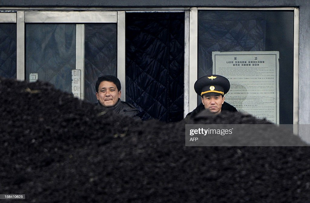 This picture taken on December 14, 2012 from China's northeastern city of Dandong, looking across the border, shows a North Korean military officer (R) and a North Korea man (L) standing behind a pile of coal along the banks of the Yalu River in the northeast of the North Korean border town of Siniuju. China is North Korea's biggest trading partner by far, and most of the business passes through Dandong in northeastern China, where lorries piled high with tyres and sacks are processed at the customs post.