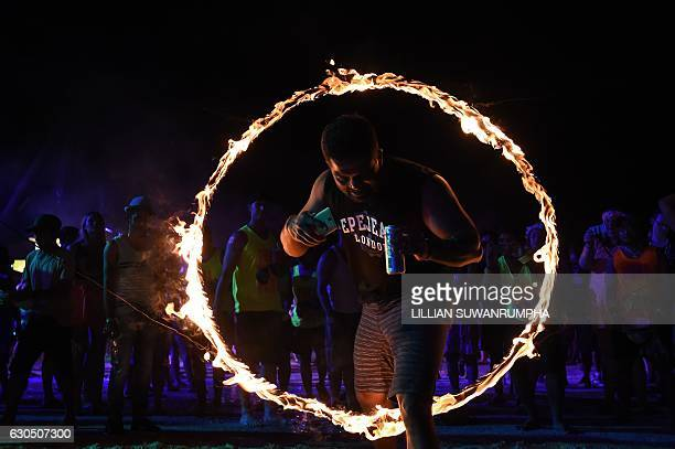 This picture taken on December 14 2016 shows a reveller walking through a hoop of fire during a Full Moon Party on the southern island of Ko Phangan...