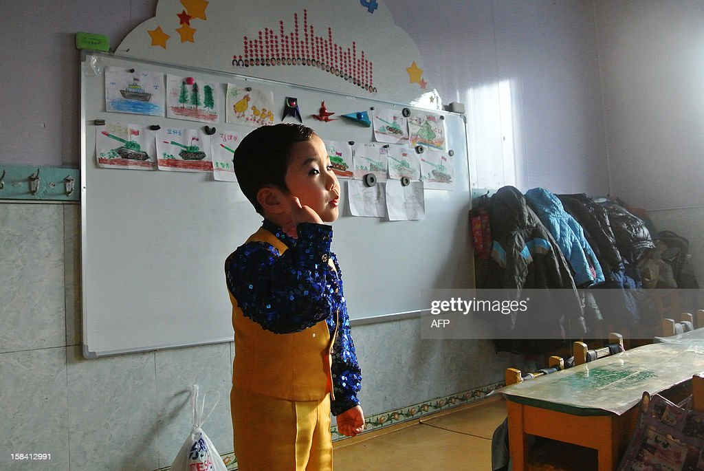 This picture taken on December 15, 2012 shows a boy singing during a music class at a nursery school in the North Korean border town of Siniuju, across from China's northeastern city of Dandong. China is North Korea's biggest trading partner by far, and most of the business passes through Dandong in northeastern China, where lorries piled high with tyres and sacks are processed at the customs post. AFP PHOTO / WANG ZHAO