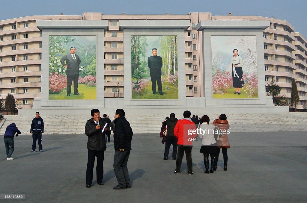 This picture taken on December 15, 2012 shows a group of Chinese looking at murals of former North Korea leaders Kim Il-sung (L) and Kim Jong-Il (C) in North Korean border town of Siniuju, across from China's northeastern city of Dandong. China is North Korea's biggest trading partner by far, and most of the business passes through Dandong in northeastern China, where lorries piled high with tyres and sacks are processed at the customs post. AFP PHOTO / WANG ZHAO