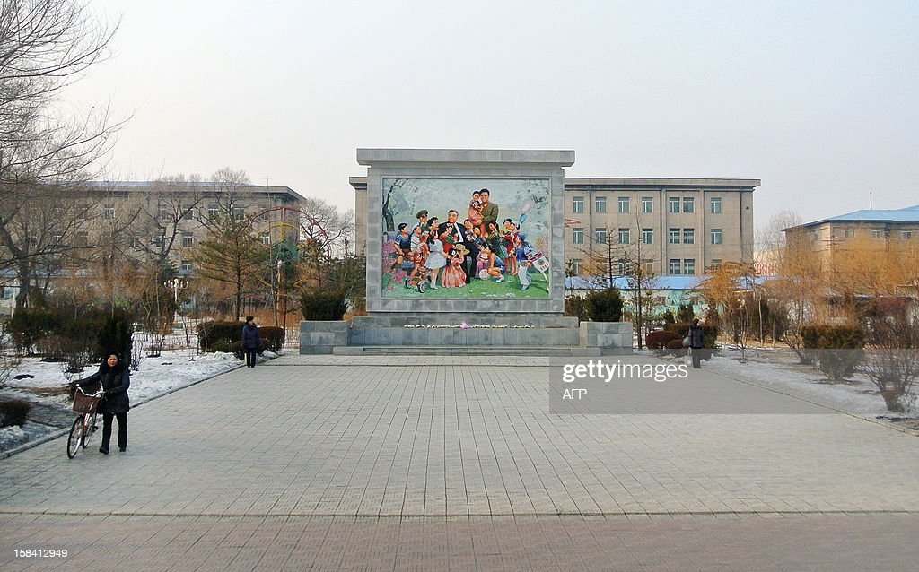 This picture taken on December 15, 2012 shows a North Korea woman (L) pushing a bicycle past a large mural in a square in the North Korean border town of Siniuju, across from China's northeastern city of Dandong. China is North Korea's biggest trading partner by far, and most of the business passes through Dandong in northeastern China, where lorries piled high with tyres and sacks are processed at the customs post. AFP PHOTO / WANG ZHAO