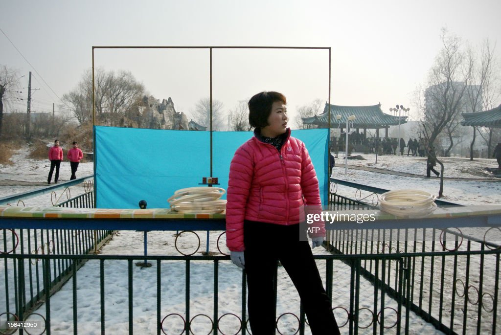 This picture taken on December 15, 2012 shows a vendor waiting for customers to play a game at a park in the North Korean border town of Siniuju, across from China's northeastern city of Dandong. China is North Korea's biggest trading partner by far, and most of the business passes through Dandong in northeastern China, where lorries piled high with tyres and sacks are processed at the customs post. AFP PHOTO / WANG ZHAO