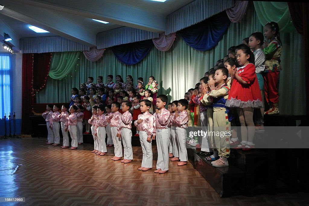This picture taken on December 15, 2012 shows North Korea children singing at a nursery school in the North Korean border town of Siniuju, across from China's northeastern city of Dandong. China is North Korea's biggest trading partner by far, and most of the business passes through Dandong in northeastern China, where lorries piled high with tyres and sacks are processed at the customs post. AFP PHOTO / WANG ZHAO