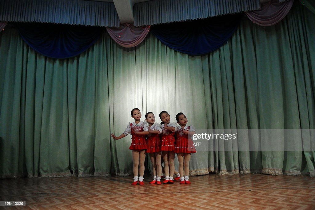 This picture taken on December 15, 2012 shows North Korean girls dancing during a performance at a nursery school in the North Korean border town of Siniuju, across from China's northeastern city of Dandong. China is North Korea's biggest trading partner by far, and most of the business passes through Dandong in northeastern China, where lorries piled high with tyres and sacks are processed at the customs post.