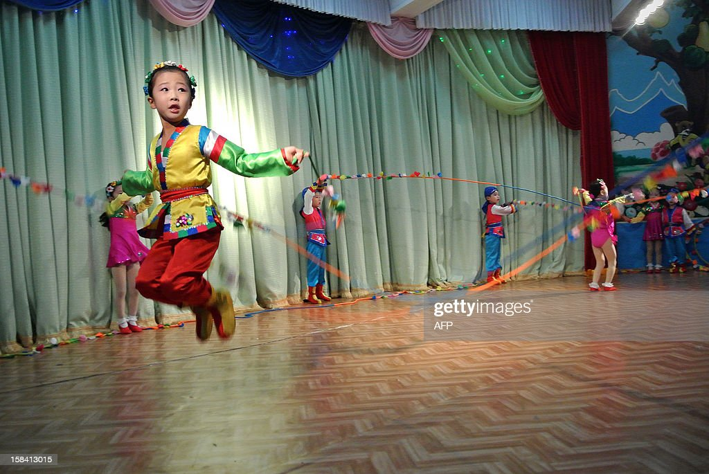 This picture taken on December 15, 2012 shows North Korean girls skipping rope during a performance at a nursery school in the North Korean border town of Siniuju, across from China's northeastern city of Dandong. China is North Korea's biggest trading partner by far, and most of the business passes through Dandong in northeastern China, where lorries piled high with tyres and sacks are processed at the customs post.