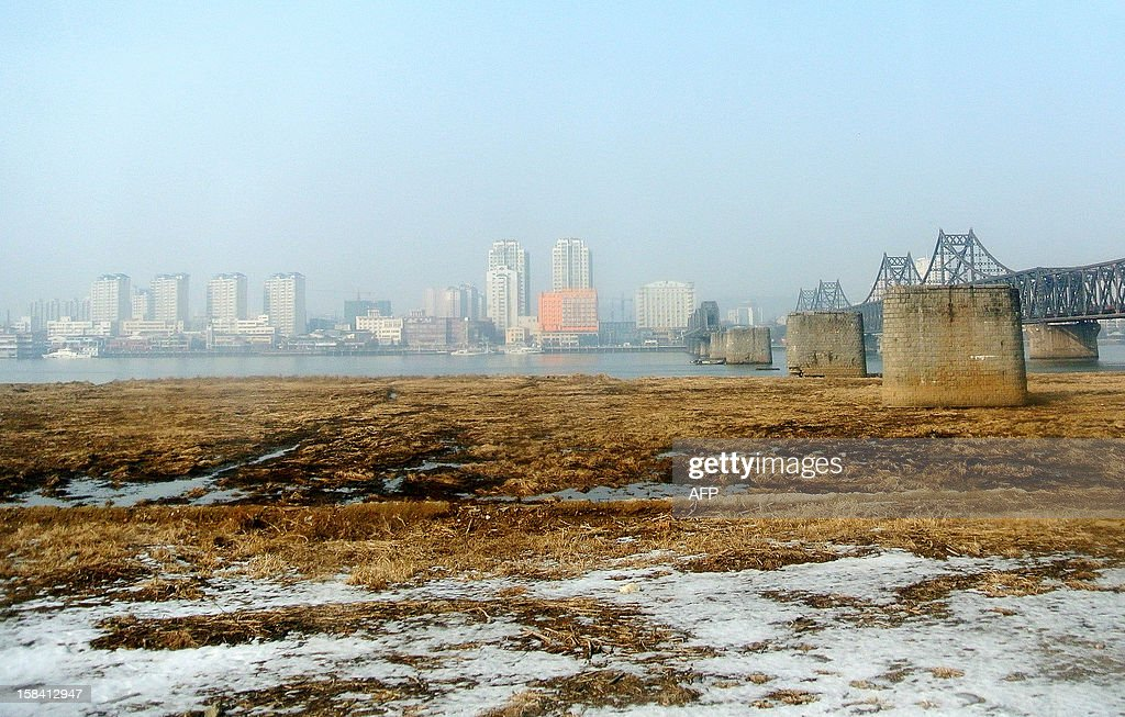 This picture taken on December 15, 2012 shows the China's northeastern border city of Dandong in the distance from the North Korean border town of Siniuju. China is North Korea's biggest trading partner by far, and most of the business passes through Dandong in northeastern China, where lorries piled high with tyres and sacks are processed at the customs post.