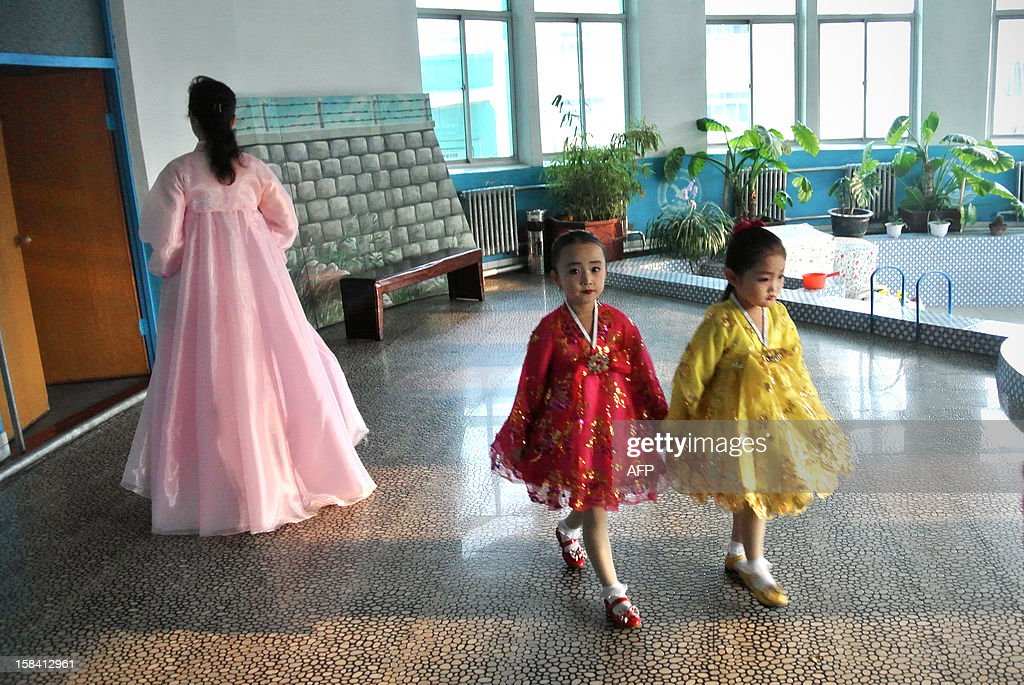 This picture taken on December 15, 2012 shows two girls making their way at a nursery school in the North Korean border town of Siniuju, across from China's northeastern city of Dandong. China is North Korea's biggest trading partner by far, and most of the business passes through Dandong in northeastern China, where lorries piled high with tyres and sacks are processed at the customs post.