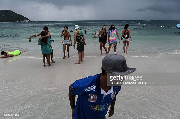 This picture taken on December 15 2016 shows partygoers continuing to rave on the beach the morning after a Full Moon Party on the southern island of...
