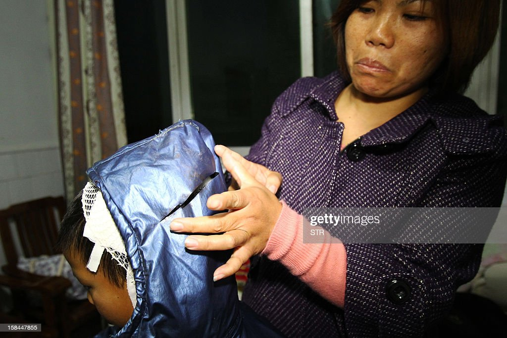This picture taken on December 16, 2012 shows a mother explaining how her son (L) got hurt during a knife attack that took place on December 14 at a primary school in Guangshan county, central China's Henan province. Internet users in China drew comparisons Saturday between violent episodes at schools in China and the US a day after 22 children were stabbed at a Chinese primary school and a US school shooting left 28 dead. CHINA