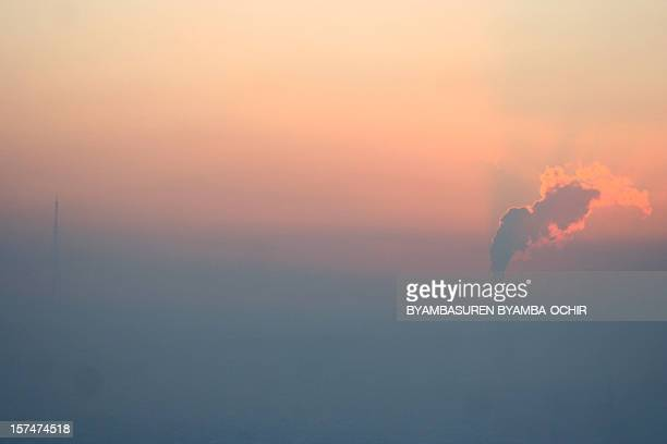 This picture taken on December 17 2011 shows smoke rising from a smokestack above the smog over the capital Ulan Bator Mongolia's economic boom has...