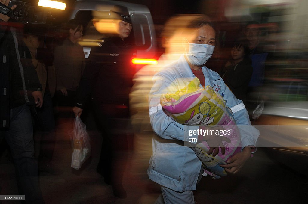 This picture taken on December 18, 2012 shows a medic (C) holding a rescued baby in her hands in Xichang, southwest China's Sichuan province. Police have detained two officials, including a family planning functionary, in China's latest crackdown on child-trafficking that has ensnared 355 suspects, state media said December 26. CHINA