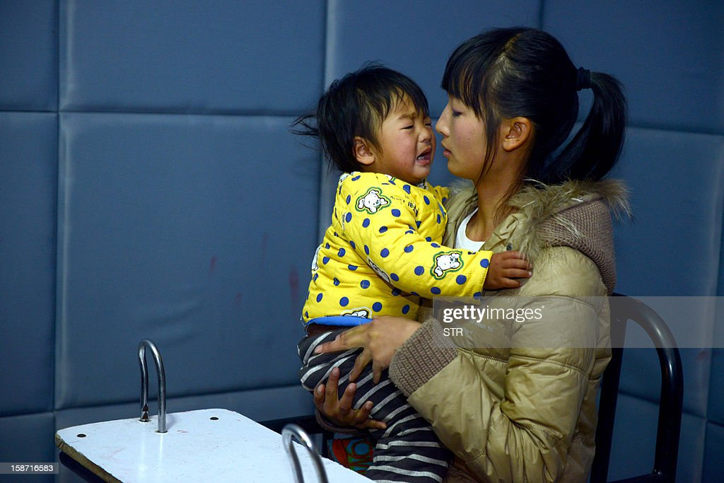This picture taken on December 18, 2012 shows a mother holding her baby in a police bureau, after she and her husband were both arrested for allegedly child trafficking other people's children, in Xichang, southwest China's Sichuan province. Police have detained two officials, including a family planning functionary, in China's latest crackdown on child-trafficking that has ensnared 355 suspects, state media said December 26. CHINA