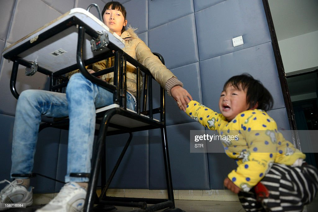 This picture taken on December 18, 2012 shows a mother holding her baby's hand in a police bureau, after she and her husband were both arrested for allegedly child trafficking other people's children, in Xichang, southwest China's Sichuan province. Police have detained two officials, including a family planning functionary, in China's latest crackdown on child-trafficking that has ensnared 355 suspects, state media said December 26. CHINA