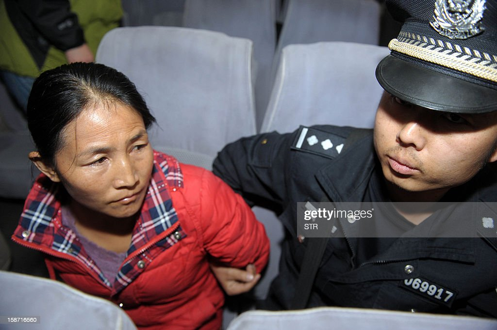 This picture taken on December 18, 2012 shows a policeman watching over a child trafficking suspect (L) in Xichang, southwest China's Sichuan province. Police have detained two officials, including a family planning functionary, in China's latest crackdown on child-trafficking that has ensnared 355 suspects, state media said December 26. CHINA OUT AFP PHOTO