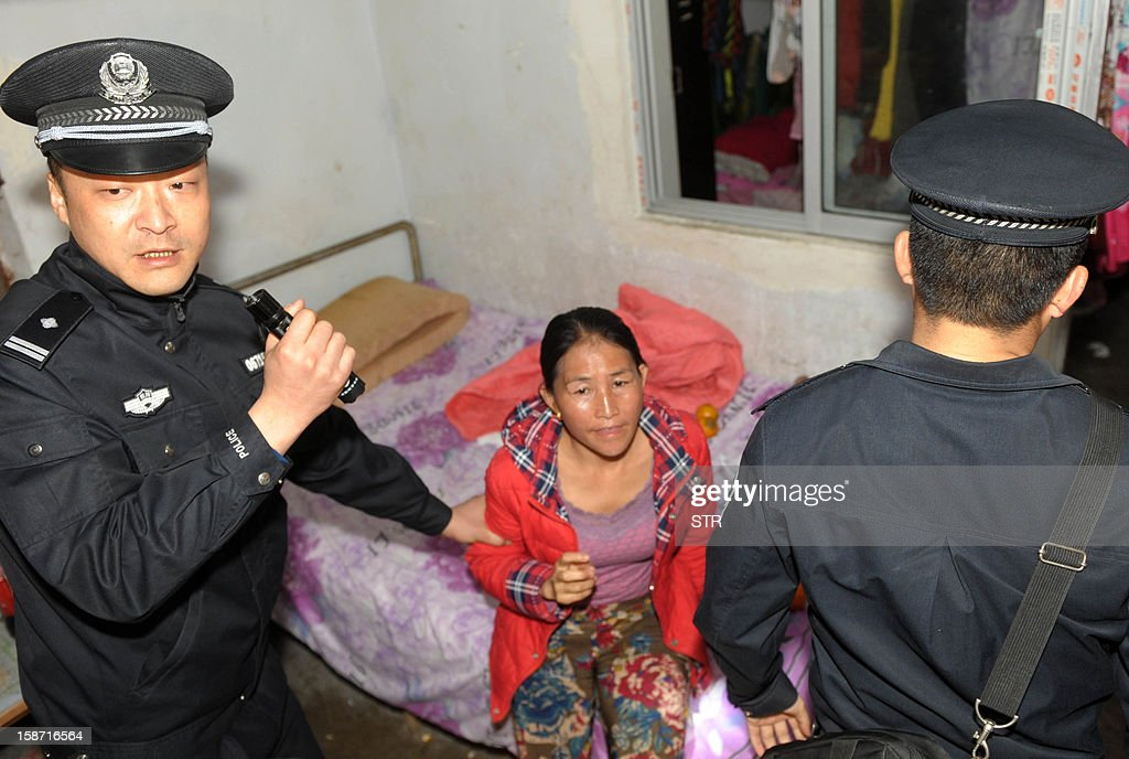 This picture taken on December 18, 2012 shows policemen arresting a child trafficking suspect (C) in Xichang, southwest China's Sichuan province. Police have detained two officials, including a family planning functionary, in China's latest crackdown on child-trafficking that has ensnared 355 suspects, state media said December 26. CHINA