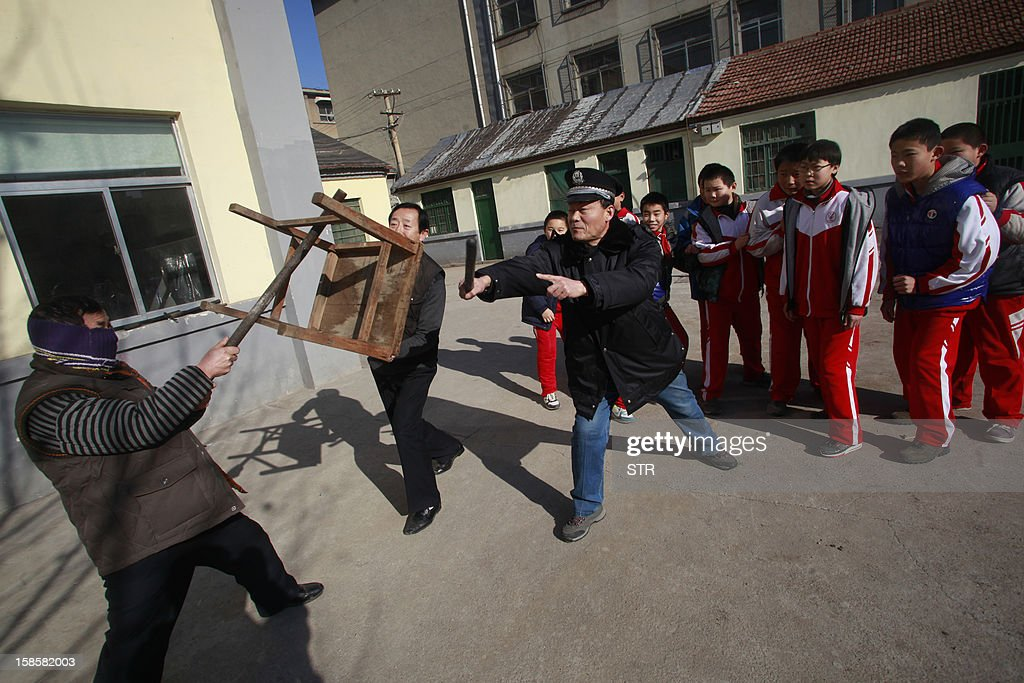 This picture taken on December 18, 2012 shows students and a guard (C) trying to stop an attacker during a drill on a mock attack at a primary school in Jinan, in eastern China's Shandong province. The drill came four days after a knife-wielding attacker stabbed 22 students at a primary school in the central Chinese province of Henan on December 14 in the latest in a series of assaults. China has seen several violent attacks against children over the past two years, including a spate of five incidents in 2010 which killed 15 children and two adults and wounded more than 80. CHINA