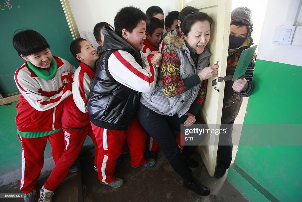 This picture taken on December 18, 2012 shows students and a teacher (2nd R) trying to stop an attacker (R) during a drill on a mock attack at a primary school in Jinan, in eastern China's Shandong province. The drill came four days after a knife-wielding attacker stabbed 22 students at a primary school in the central Chinese province of Henan on December 14 in the latest in a series of assaults. China has seen several violent attacks against children over the past two years, including a spate of five incidents in 2010 which killed 15 children and two adults and wounded more than 80. CHINA OUT AFP PHOTO