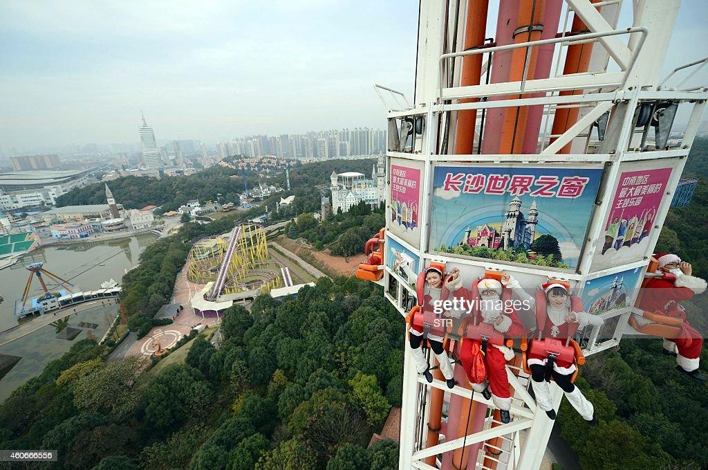 This picture taken on December 18 2014 shows employees wearing Christmas costumes on a freefall ride at a theme park in Changsha central China's...