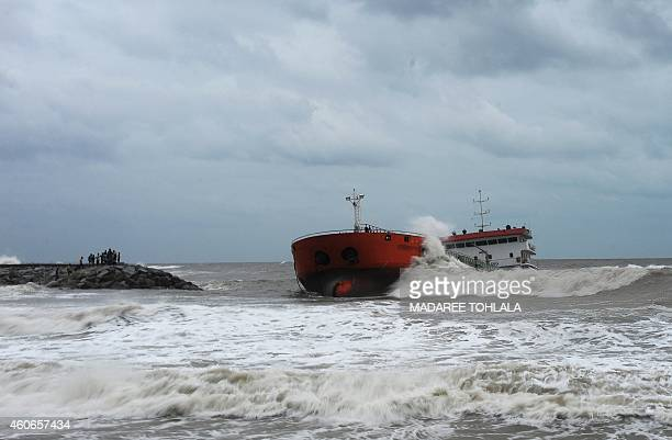 This picture taken on December 18 2014 shows residents watching as an Indonesiaregistered tanker lies in rough sea close to the shore after it was...