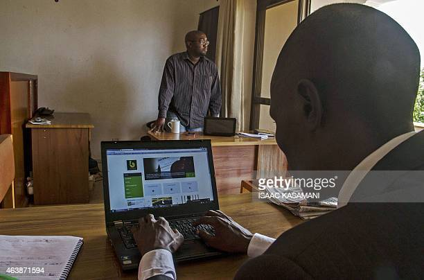 This picture taken on December 19 2014 shows Gerald Abila the Managing Director of Barefoot Lawyers and Michael Kwizera the head of Strategy and...
