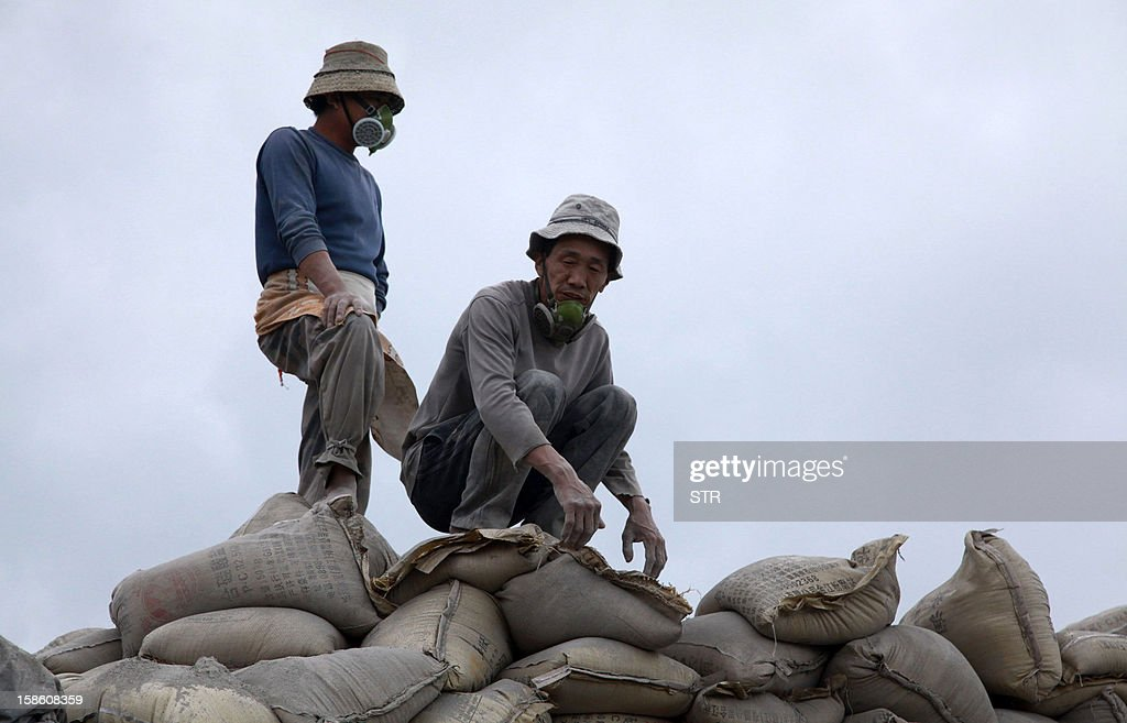 This picture taken on December 20, 2012 shows labourers pausing as they unload bags of cement at a port in Haikou, in southern China's Hainan province. China said on December 18 it faces a bleak foreign trade environment in 2013 due to ongoing global economic weakness, as the Asian export powerhouse appears set to miss this year's trade growth target. CHINA OUT AFP PHOTO