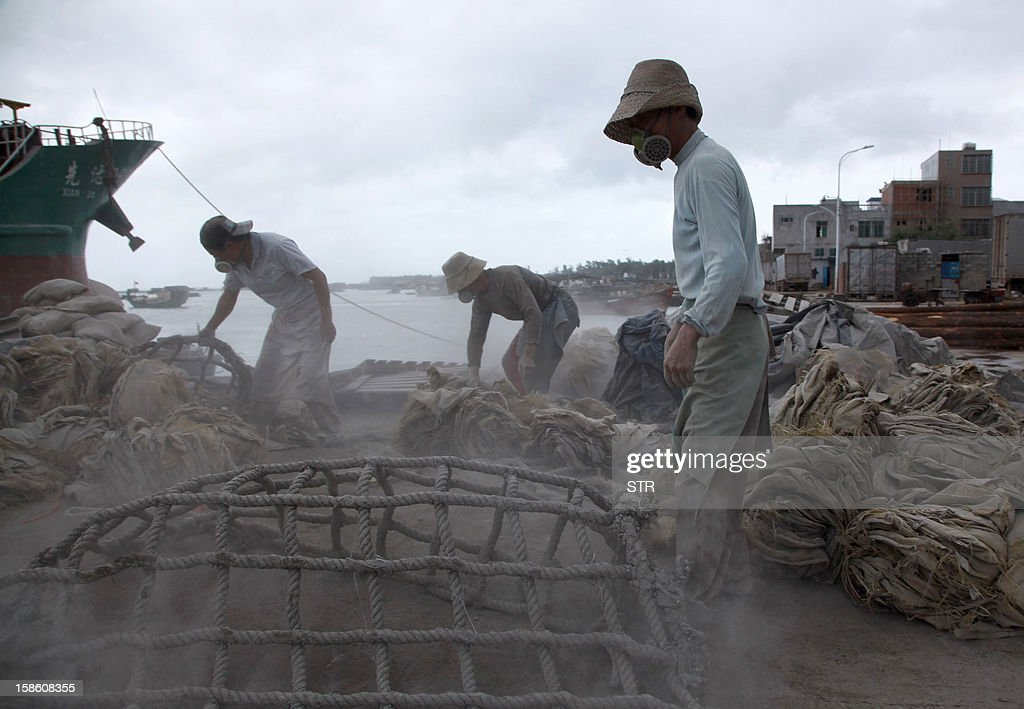 This picture taken on December 20, 2012 shows labourers unloading cement at a port in Haikou, in southern China's Hainan province. China said on December 18 it faces a bleak foreign trade environment in 2013 due to ongoing global economic weakness, as the Asian export powerhouse appears set to miss this year's trade growth target. CHINA OUT AFP PHOTO