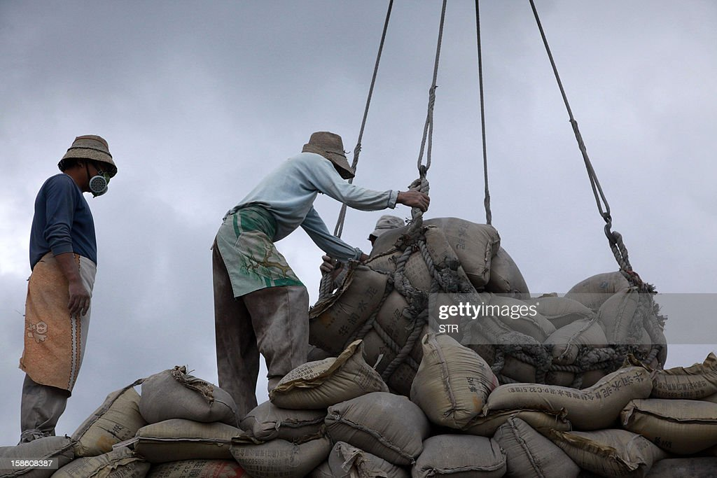 This picture taken on December 20, 2012 shows labourers unloading bags of cement at a port in Haikou, in southern China's Hainan province. China said on December 18 it faces a bleak foreign trade environment in 2013 due to ongoing global economic weakness, as the Asian export powerhouse appears set to miss this year's trade growth target. CHINA OUT AFP PHOTO