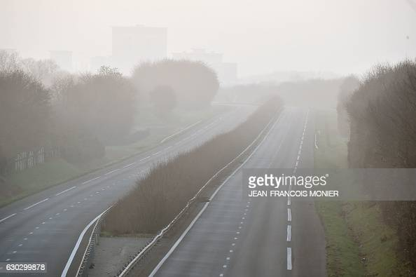 This picture taken on December 20 2016 shows the fog on the road next to the site where a car accident involving around fifty vehicles killed 5...