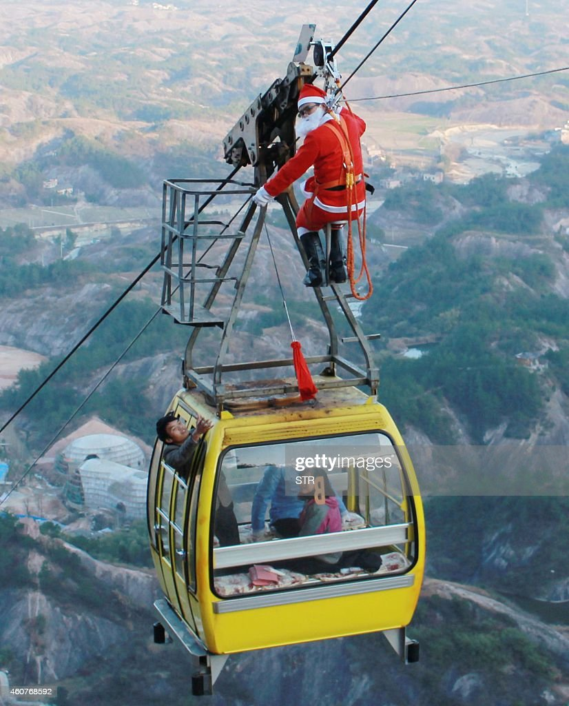 This picture taken on December 21 2014 shows a man dressed up as Santa Claus hanging from a cableway as he delivers Christmas gifts to visitors in a...