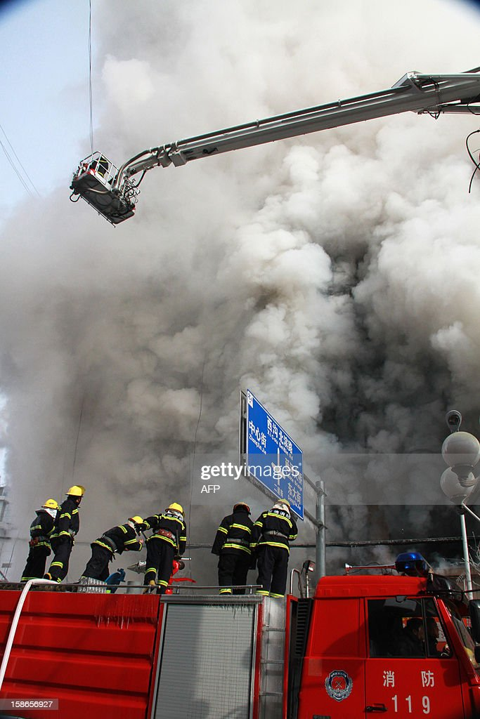 This picture taken on December 22, 2012 shows firemen attempting to control a fire at the World Trade Building in downtown Yan'an, northwest China's Shaanxi province. Two people were killed and 20 injured when the fire swept through this 14-storey office tower, state media reported. CHINA