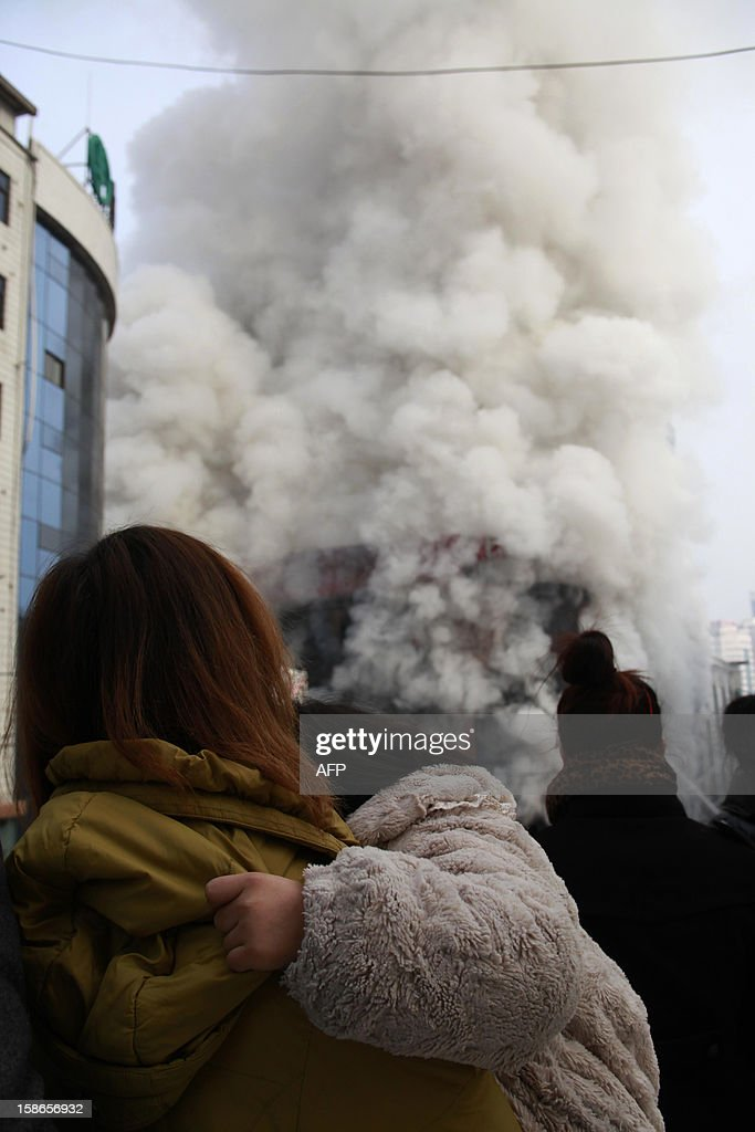 This picture taken on December 22, 2012 shows people watching as firemen attempt to control a fire at the World Trade Building in downtown Yan'an, northwest China's Shaanxi province. Two people were killed and 20 injured when the fire swept through this 14-storey office tower, state media reported. CHINA OUT AFP PHOTO
