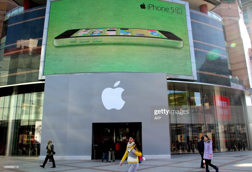 This picture taken on December 22, 2013 shows shoppers walking past the Apple store in Beijing. Apple has unveiled a long-anticipated deal with China Mobile, the world's biggest wireless carrier, to bring the iPhone to customers in a market dominated by low-cost Android smartphones.