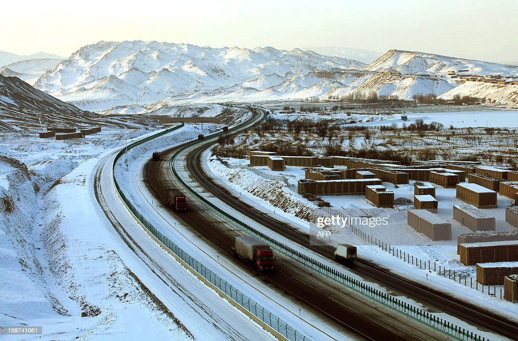 This picture taken on December 23, 2012 shows the snow-covered roads and mountains in Tulufan, northwest China's Xinjiang province. A fresh cold snap is hitting most parts of China recently, according to the National Meteorological Center's forecast on December 26. CHINA