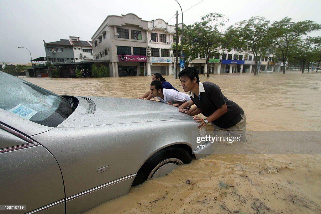 This picture taken on December 24, 2012 shows flood victims pushing their car through the flooded streets in Malaysia in the northeastern town of Kuantan. A woman drowned in a swollen river while fishing as flash floods hit Malaysia's northeastern states triggered by the country's annual heavy monsoon rains, the official Bernama news agency said.