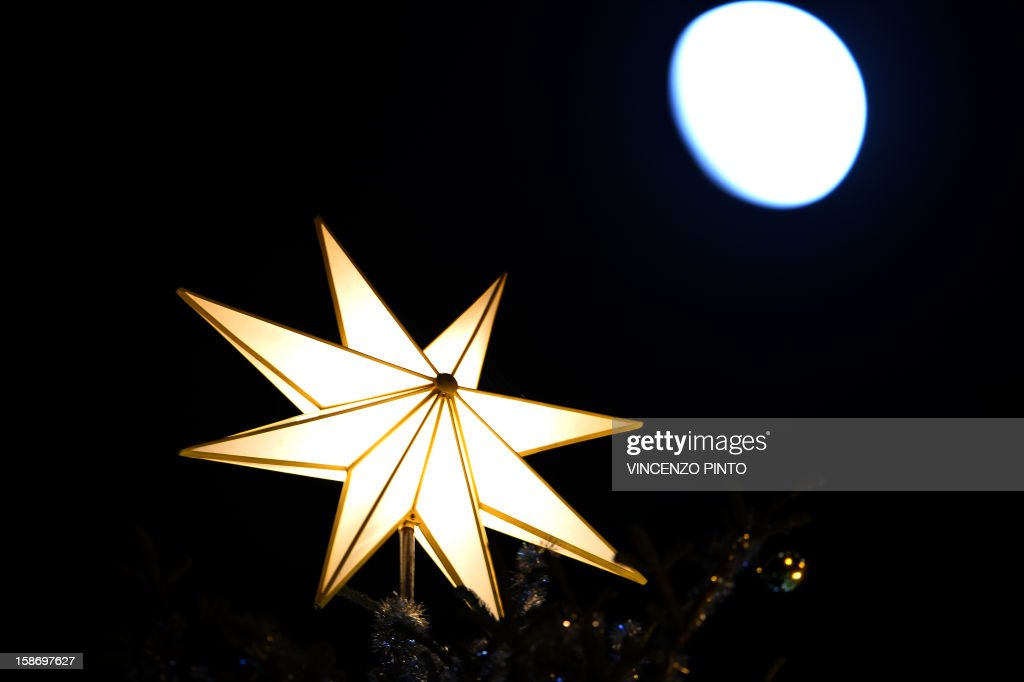 This picture taken on December 24, 2012 shows the moon next to the crib's star, during the unveiling ceremony of the crib in St Peter's Square at the Vatican. Pope Benedict XVI will celebrate a late Christmas night holy mass at St. Peter's Basilica to mark the nativity of Jesus Christ.