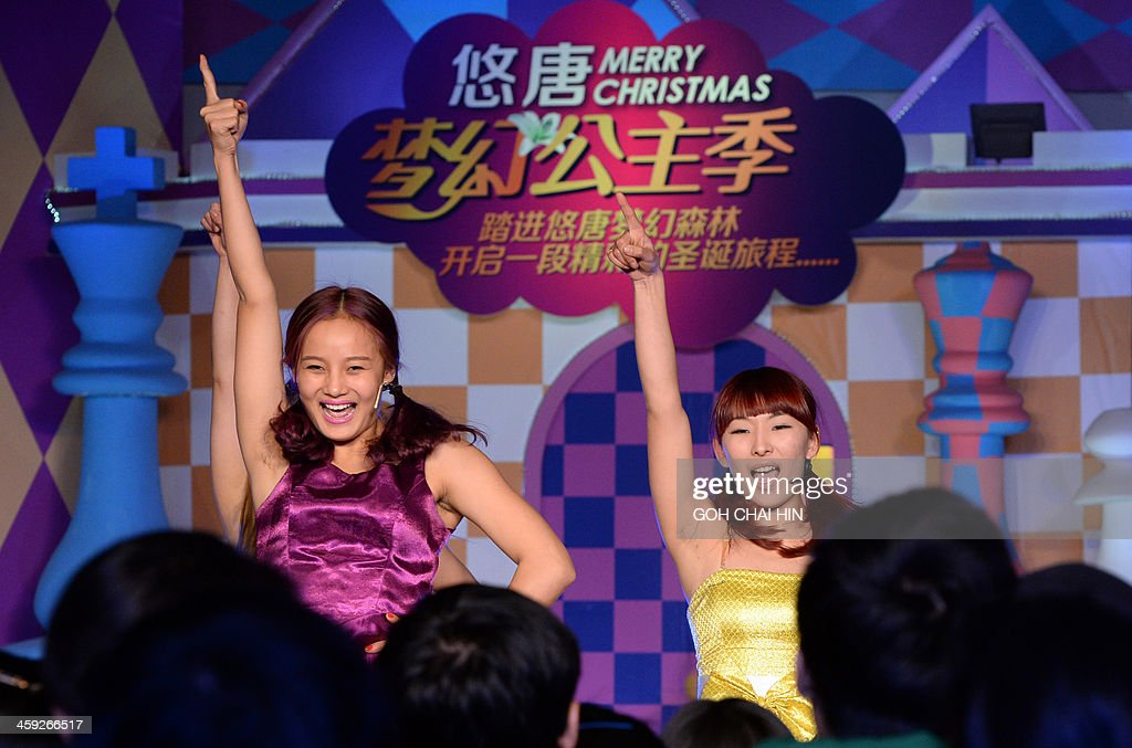 This picture taken on December 24, 2013 shows performers dancing at a Christmas gala at a shopping mall in Beijing, as Chinese businesses cash in on the commercial value of the Christian festival. Annual growth rates above 10 percent were once common during China's metamorphosis from a classic communist-style command economy to the state-private hybrid unleashed by reforms introduced by Deng Xiaoping in the late 1970s, and in the process, hundreds of millions of Chinese were lifted out of poverty as the economy enjoyed a decades-long boom. AFP PHOTO/GOH CHAI HIN